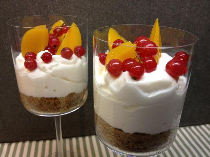 Crema di yogurt in bicchiere con fondo di biscotto croccante, ribes e pesche sciroppate