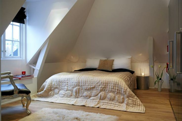 Sengen er lav, med et stort sengeteppe som blir liggende utover gulvet. Veggen på den ene siden av sengen dekkes av blanksvarte garderobeskap, mens resten av vegger og tak holdes i hvitt. Det bratte skråtaket skaper en spennende dynamikk.