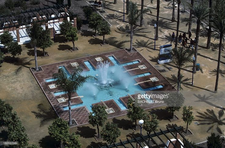 Universal Exposition Of Seville 1992 Water And Air Conditioning. A l'Exposition Universelle de Seville, sur une place plantée d'arbres un bassin carré envoyant des jets d'eaux. .