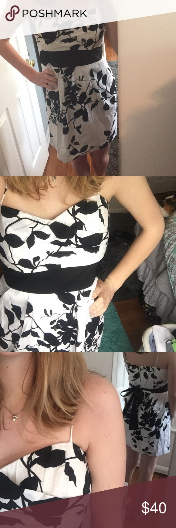 Black and white special occasion dress Black and white dress with adjustable straps and an attached black belt with a flower on it. It has pockets too! Perfect for those special occasions when you want to be comfortable and cute. delia*s Dresses