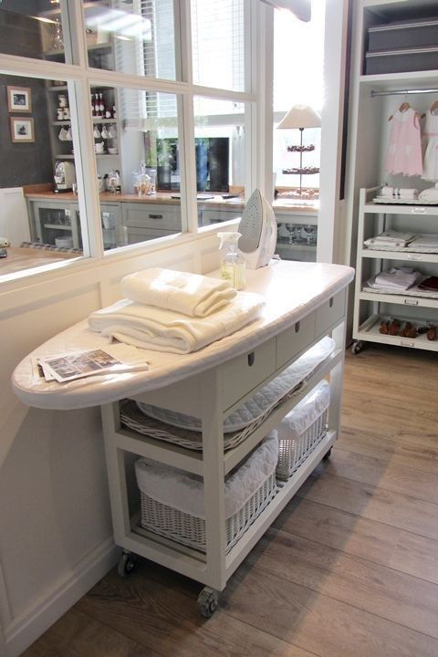 I adore the idea of an ironing board with laundry stuff below - and it's on wheels!  Probably going to go for a less rustic look.