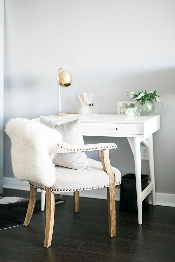 Chic home office with light gray walls, a white desk, a gold task lamp and a lamb throw