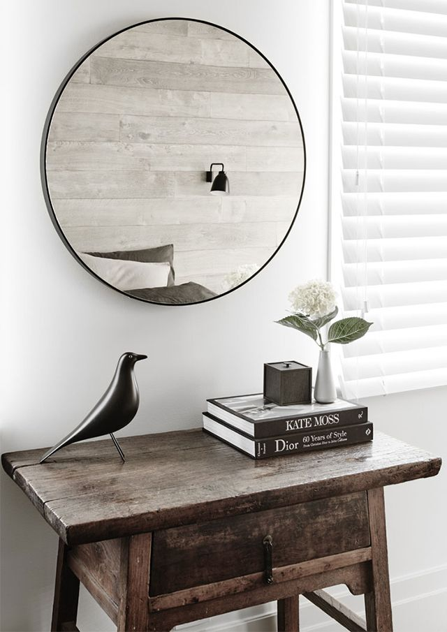 An elegant, understated modern farmhouse - recycled wooden coffee table and a round mirror above, rustic and elegant