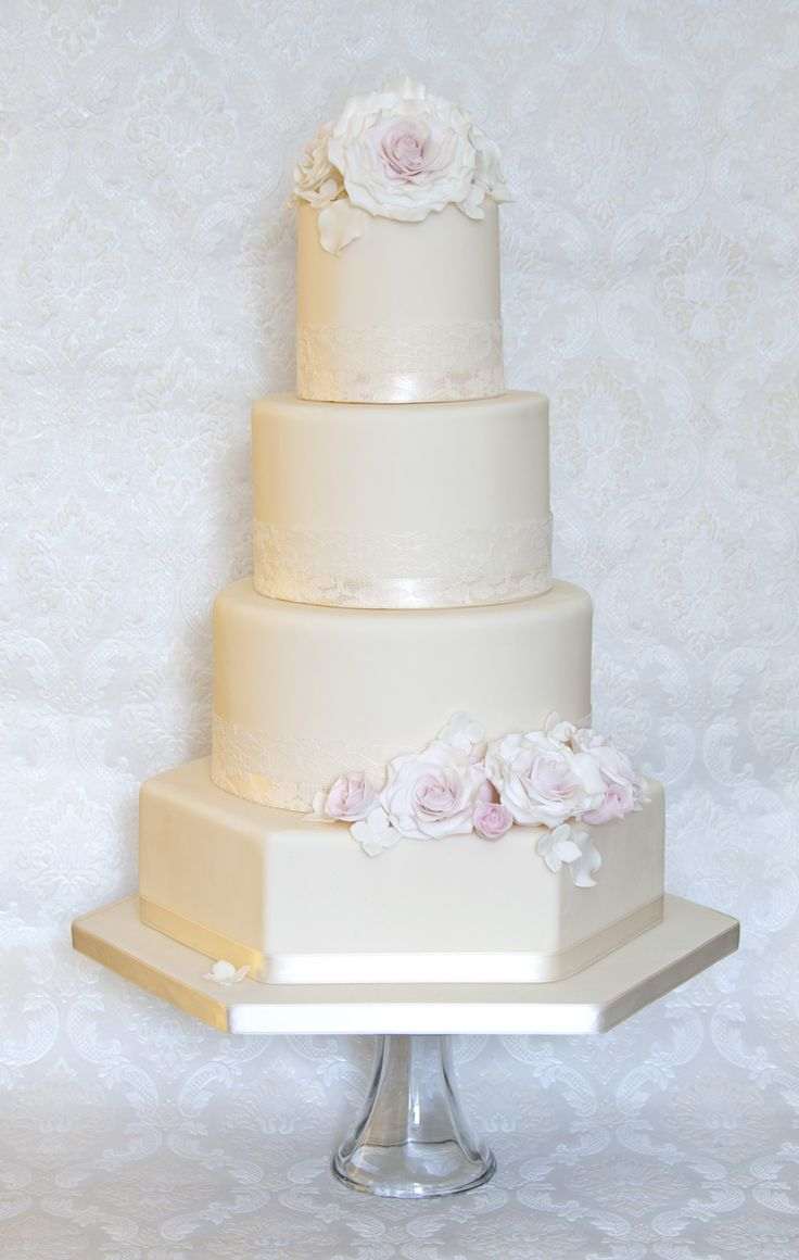 The vintage cake is a classic design using a hexagonal base tier to add a little more interest. Ivory lace and soft pink roses complete the vintage look.By Cherry Blossom Cakes. For more inspiration visit www.weddingsite.co.uk
