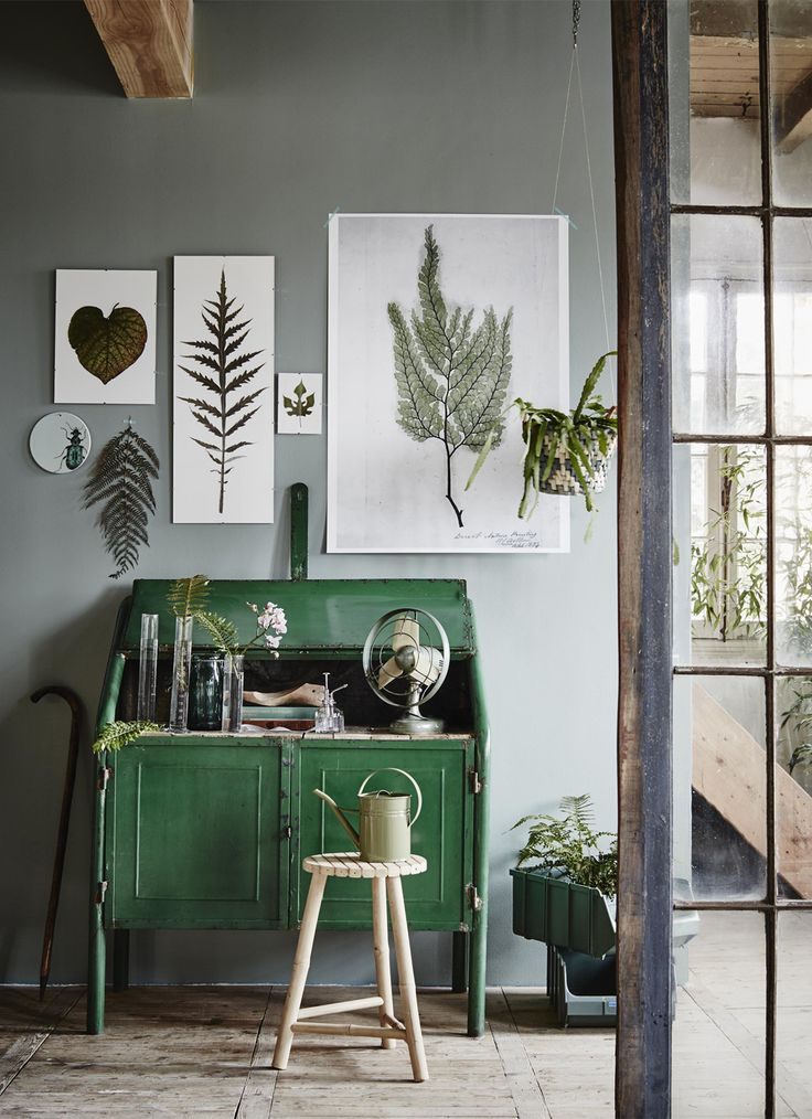 botanical leaf art on wall above desk and wooden stool