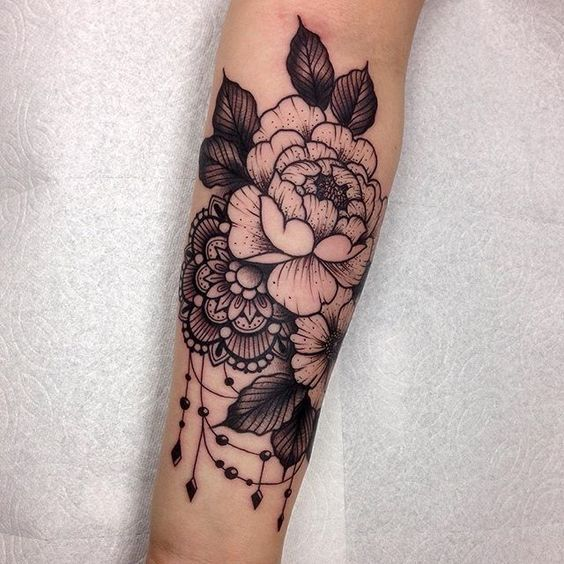 Intricate flower and lace arm tattoo. Click to discover more Sensational Flower Tattoos.