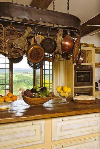 love this rustic country kitchen look with a hint of French Country...notice all the different things they have hanging from the pot rack
