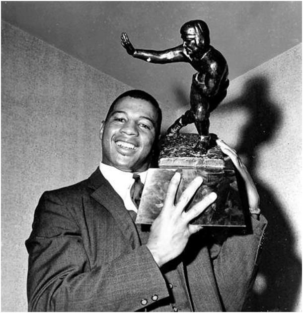 Ernie Davis with the Heisman Trophy in 1961. Ernie Davis is best known for being one of the greatest football players in college football history and the first Black person to win the Heisman trophy. In the process, Davis became an icon for an integrated America and for African Americans achieving the American Dream in a manner similar to Jackie Robinson desegregating Major League Baseball in 1947.