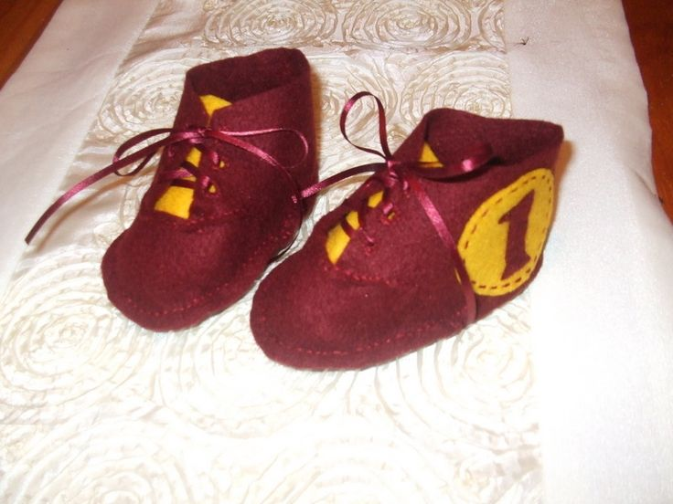 I made this pair for a lady were the new daddy was a Broncos supporter, hence the colours and I appliqued baby's initial on outer side of one boot and the number one on the other one. Made from soft felt and we found they stay on better than little soft shoes.