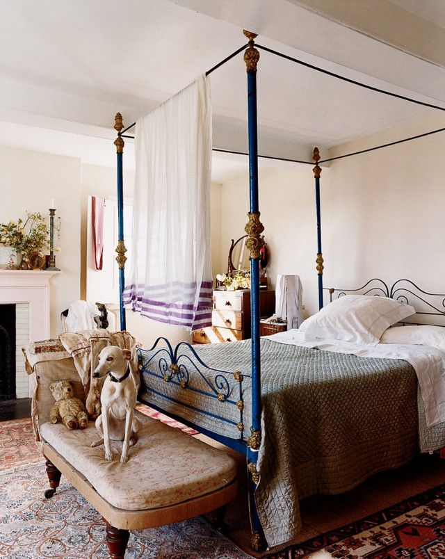A 19th-century gold and blue Moroccan bed takes center stage in the English  country