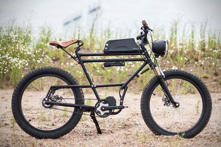 """スクランブラーというと、トライアンフやドゥカティなどの旧車をオフロード仕様にしたイメージがありますが、これは""""Eバイク""""。つまり電動アシスト自転車です。 しかし、ベースとなるフレームには、1930年代の荷物運搬用自転車のものを使っていますので、「旧車がベース」という意味では似ています。つまり、ビンテージかつオフロードテイスト溢れる装備と、電動モーターなど今のテクノロジーを融合させた電動自転車がこの「スクランブラーEバイク」なのです。 スクランブラーEバイク このEバイクには、プーリー左側に電動モーターが装備されていますので、オフロードや街の坂道でも、あくせくペダルを漕がずに快適に走れるのが魅力です。最高速度はモーターの仕様により25km/hバージョンと45km/hバージョンがあり、いずれも3速ギアを採用しています。 また、前後ディスクブレーキも装備していて、制動性能も抜群。走りに関しては最新のアイテムが採用されています。 Eバイクなので、バッテリー残量も気になるところ。そこでこの「スクランブラーEバイク」には、デジタル液晶メーターが装備されており、バッテリーの..."""