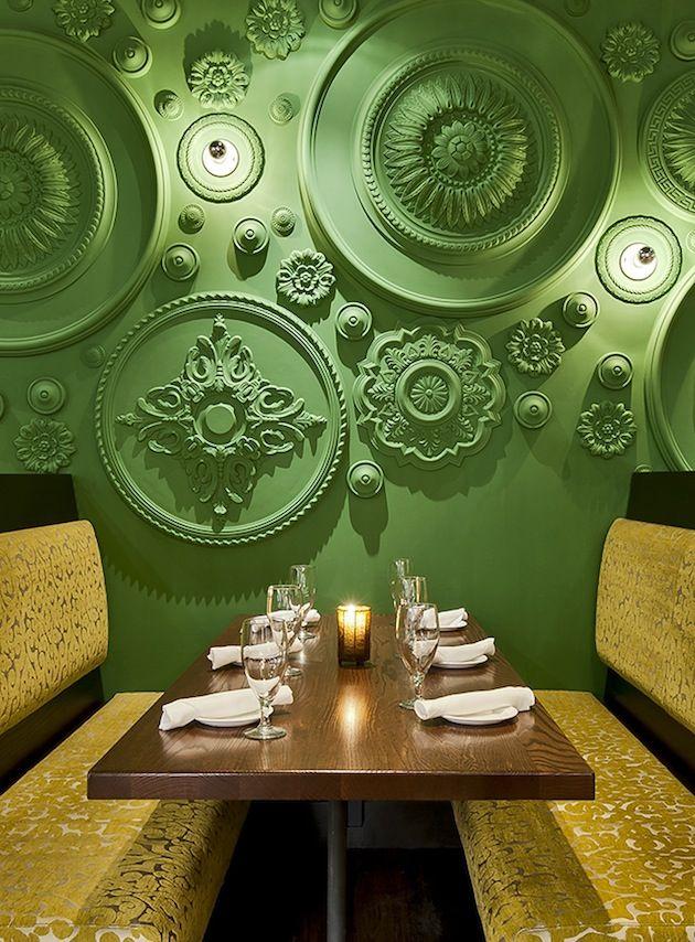De muren en het plafond van Restaurant Barbatella zijn van boven tot onder gedecoreerd met groene plafondrozetten