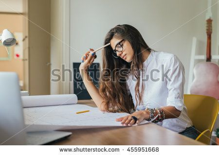 Getting it all done from home.young woman working on a blue prints in her home office