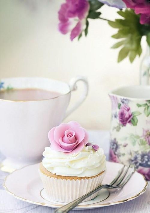 A cupcake with white frosting and a pink rose served on a small plate. Just as it should be.