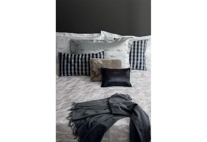 Sul copripiumino Flying Shell in seta e cotone jacquard di La Perla Home Collection (in collaborazione con Fazzini) tanti cuscini in fantasie, tessuti e colori diversi