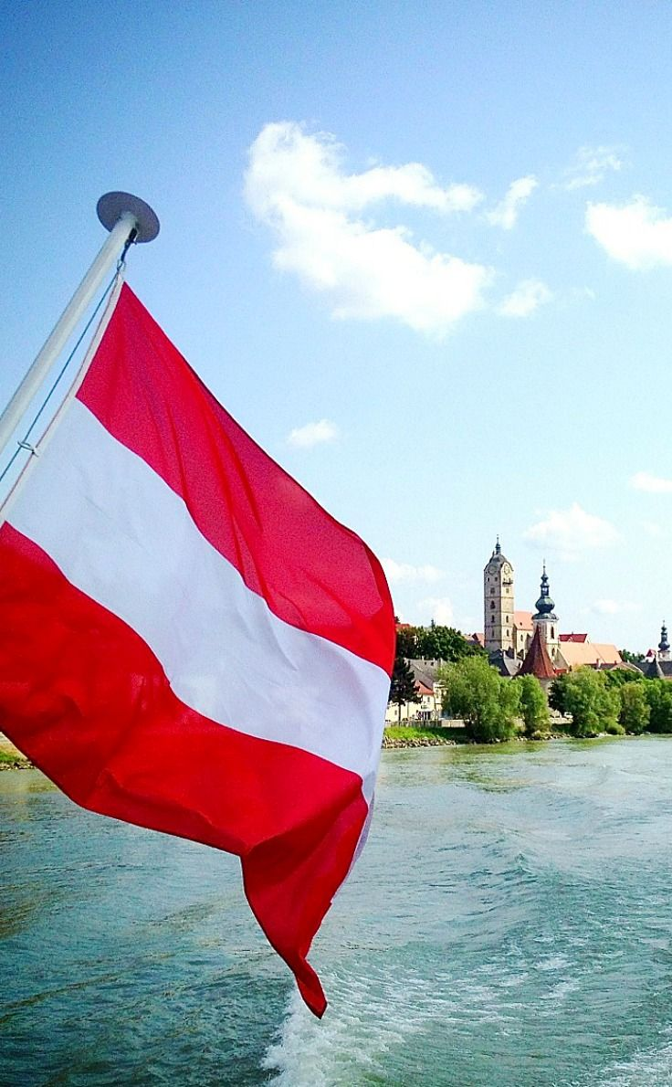 Sailing on the Danube in Lower Austria past the town of Dürnstein, the Austrian flag flying on the breeze. There are many ways to see the Danube in Austria - here's five, from cycling to segways, wine walks to vintage trains.