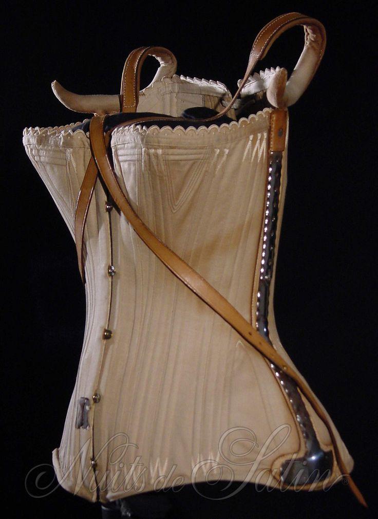 Corset orthopédique 1890' en coutil beige, avec 2 soutiens de hanche en acier nickelés et 2 sangles épaule en cuir, évantaillé  et orné d'un croquet brodé de coton beige, gorge baleinée, doublé et comportant 94 baleines dont 62 baleines courtes latérales - Busc de 33 cm avec 5 attaches - Tour de taille 54 cm.