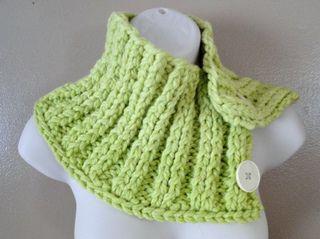 Tour de cou fait d'un rectangle tricoté de haut en bas en double côtes et boutonné sur le côté.