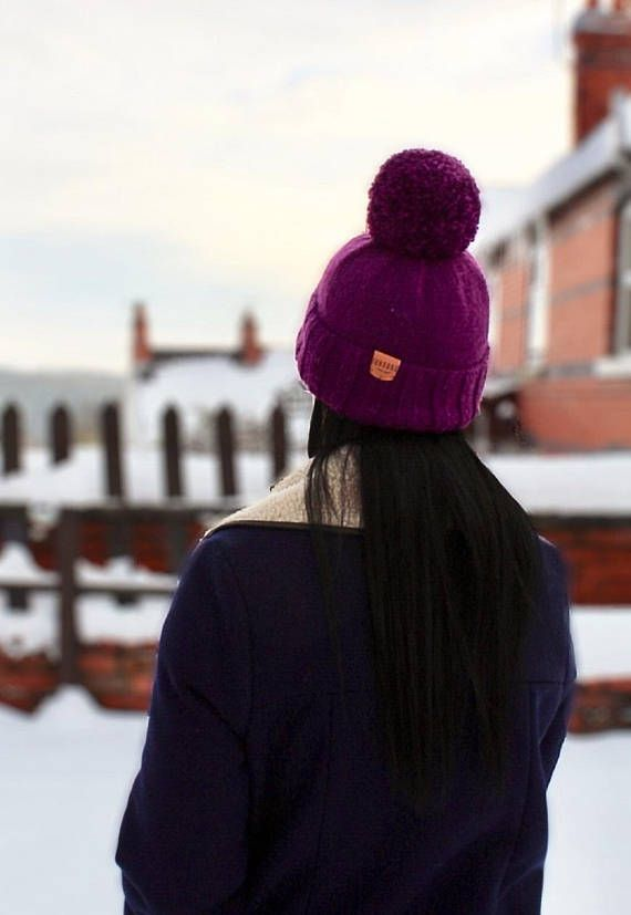 Unique one off handknitted bobble hat in magenta purple. Each piece is knit by hand in our North Wales studio so every hat is unique. Finished with a Junkbox Ultraleather tag. Wool/Acrylic blend. Unisex style. One size fits all. THE Winter accessory!!! (Co-ordinating items are