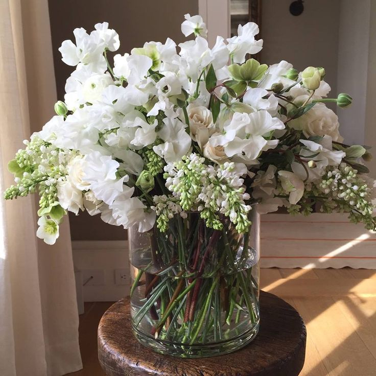 all-white sweet peas, ranunculus, lilacs, and hellebores, with a few green leaves that set off the white flowers beautifully