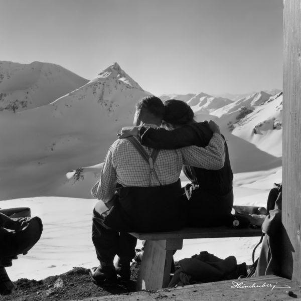 Verliebtes Pärchen blickt auf die verschneite Bergwelt. Jetzt viele weitere…