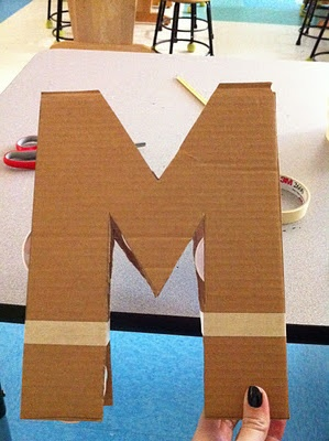 Step 1: Cut out letter in card board Step 2: Support letter with dixie cups Step 3: Fully tape edges Step 4: Make a glue/water solution to dip newspaper strips in.  Make sure letter is fully wrapped and coated with glue mixture.