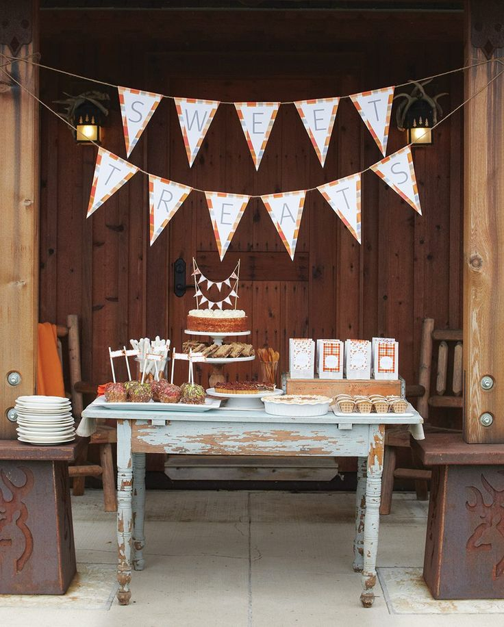 A weathered old table is set up under a festive banner for a treat table at a casual outdoor fall party.