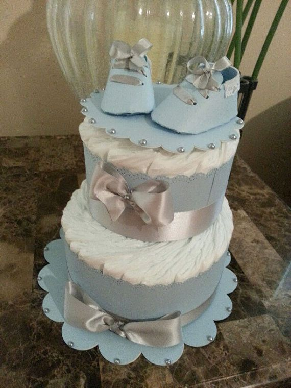 This beautiful two tier diaper cake for a baby boy will make a beautiful accent or even work as the central centerpiece if you have multiple tables. Another idea gift your shower recipient something tasty from the bakery by surprising her with this elegant cake. It will definitely make a lasting impression. The cake includes 40 size one diapers a cake plate and shoe cake topper.  **********Help prevent delays in Delivery***********  I want to thank you for allowing The Carriage Shoppe to be…