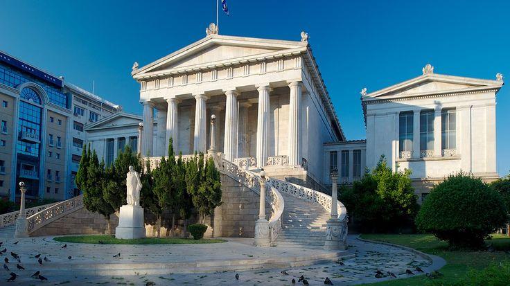"""L'imponente Biblioteca Nazionale è il più orientale dei tre edifici che formano la cosiddetta """"Trilogia Ateniese"""": la Biblioteca, l'Università di Atene e l'Accademia di Atene. La Biblioteca fu progettata da Theophil Hansen e finanziata dalla famiglia Vallianos, uomini d'affari greci della diaspora."""