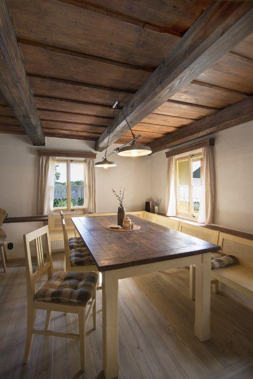 Velké světnici vévodí jídelní stůl s dubovou deskou, nad níž je dvojsvětlo vyrobené na zakázku firmou od Dačic.