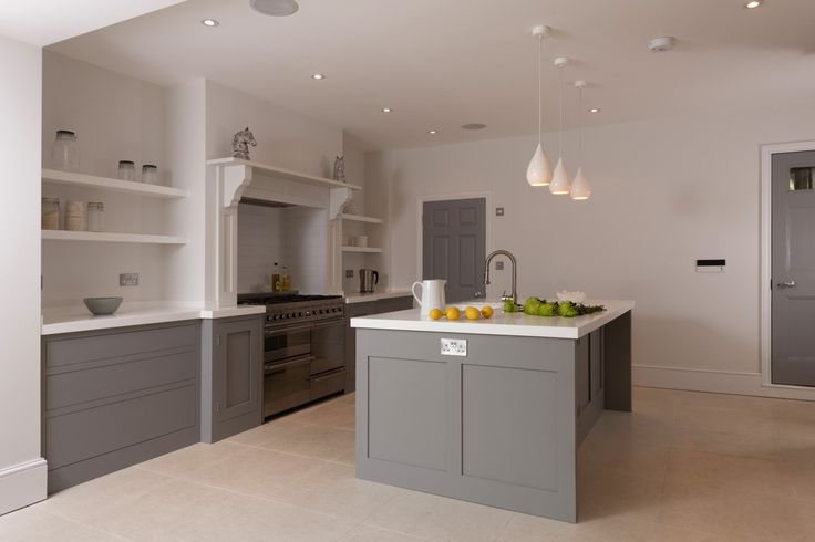 Painted handleless shaker cabinetry mixed with a real chimney, range cooker, light flooring and crisp white Corian worktops make this kitchen a lovely mix of the traditional and contemporary.