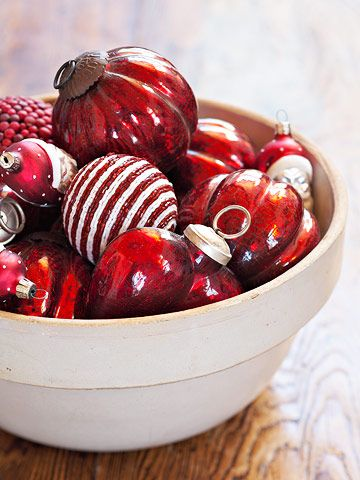 Bowl of Cheer --   Traditional glass ornaments in classic red and white make a simple and sophisticated decoration when piled in a white bowl or pot.