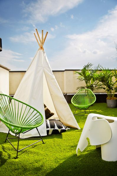 Garden - A tepee, two Baby Acapulco Chairs in Cactus, and an Eames elephant on a rooftop patio covered with synthetic lawn