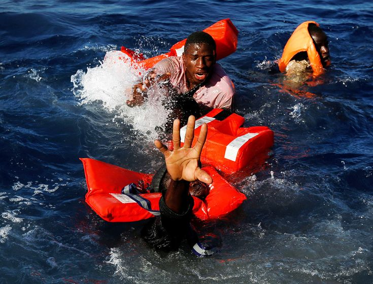 Migrants struggle to stay afloat after falling off their rubber dinghy during a rescue operation by the Malta-based NGO Migrant Offshore Aid Station in the Mediterranean international waters some 15 nautical miles off the coast of Zawiya in Libya on April 14.  Darrin Zammit Lupi / Reuters
