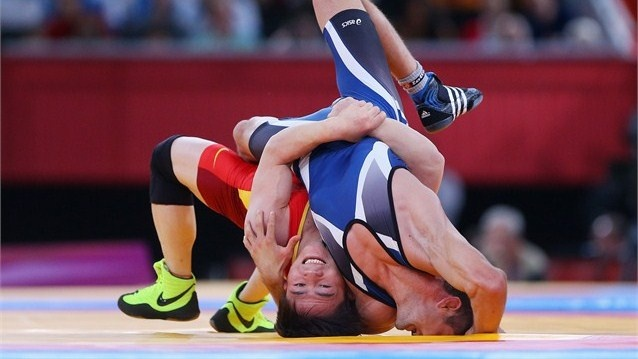 Ivo Serafimov Angelov of Bulgaria competes against Jiang Sheng of China (L) during the men's Greco-Roman 60kg Wrestling Repechage on Day 10 of the London 2012 Olympic Games at ExCeL