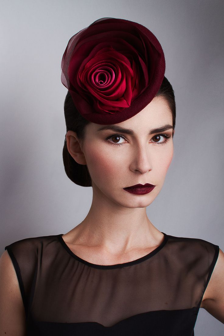 ROSE PETALS £295.00  Handcrafted in our London studio.  Peachbloom felt cocktail hat with hand dyed silk layers.  Colours: Plum, Burgundy, Red.  Secured with a comb and elastic.  1 in stock.  UK delivery 3-5 working days.  Sent free within the UK. Includes a Black & White striped hatbox.