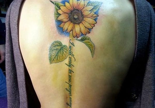 An artistic and lovely sunflower tattoo design. The sunflower is seen to be on the top part of the back while the stem is composed of calligraphy which is a very creative way of putting the quote.