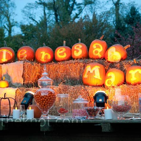 the candy buffet outside the reception tent was decorated with lit up pumpkins carved to halloween candy barideas