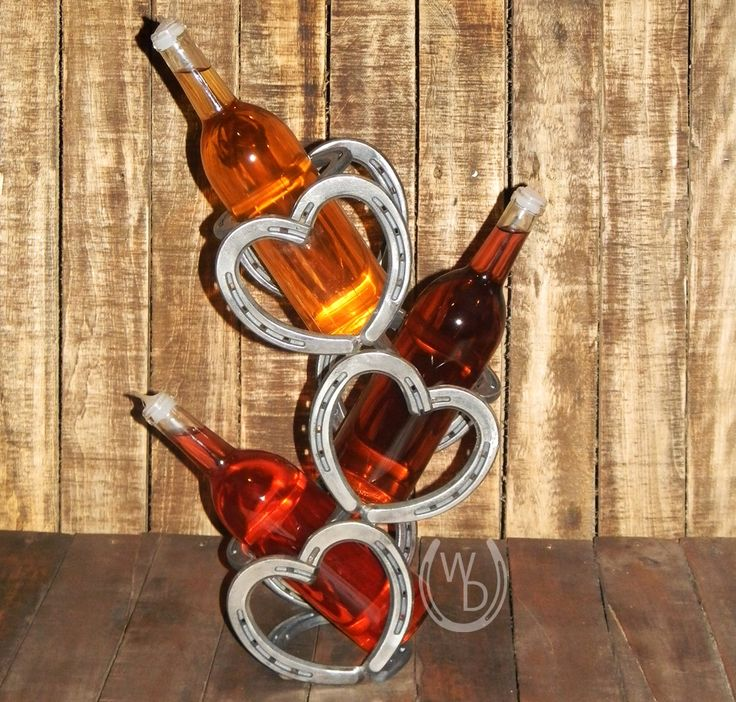 Wine bottle holder from recycled horse shoes. Bent into heart designs.