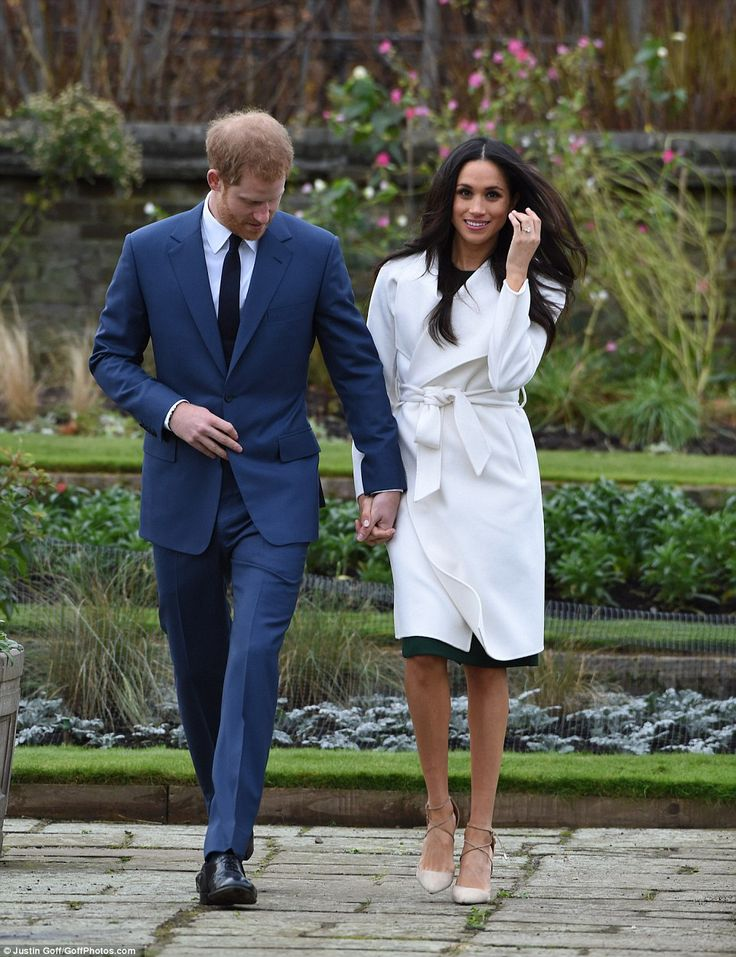 Harry grips his fiancee's hand as they walk over paving slabs in the London garden as she flicked hair out of her face