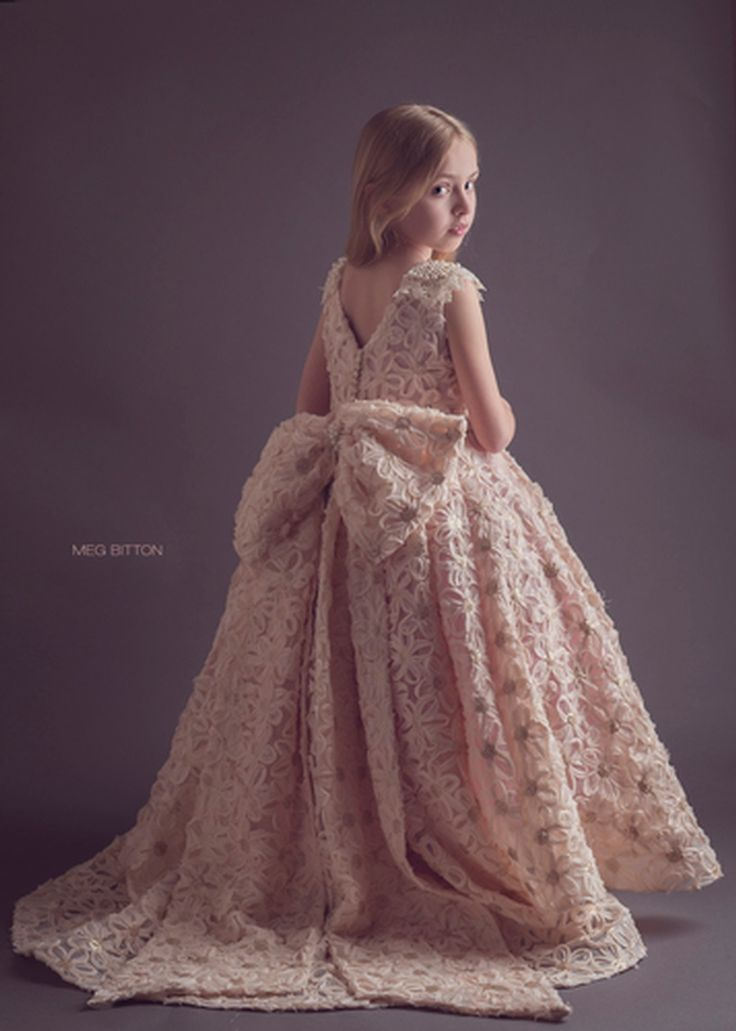 A stunning gown from top to bottom. Exquisite rosette fabric in pale blush with matte sequins in centers, gorgeous double circle skirt with long train in the back, full underskirt made of tulle and silky satin, pearl beading at neckline, detachable bow in the back. Button closure.