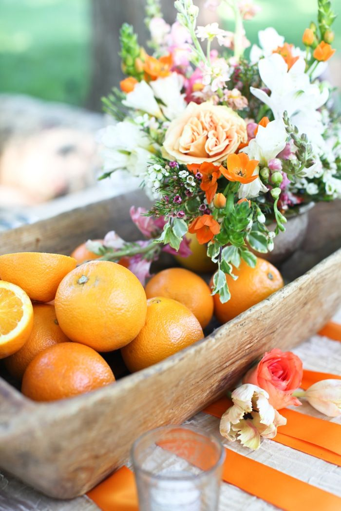 oranges and flowers - this is a great idea...  old wooden troughs or boxes with piles of fruit, then with a very small floral and fresh herb arrangement tucked in next to the fruits and veggies