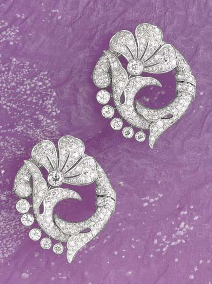 A Pair of Art Deco Diamond and Platinum Double-Clips, Circa 1930. Designed as a papyrus flower decorated with old-cut diamonds, mounted in platinum, 4.8 x 4 cm. #ArtDeco