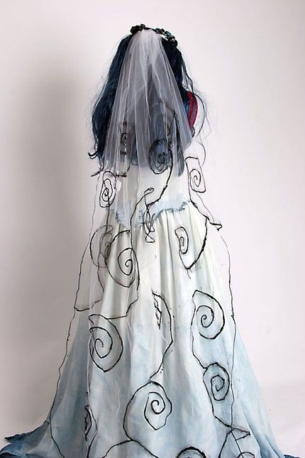 The Corpse Bride Veil is made of a layer of tulle and hand painted with black Burton swirls. It is attached to a headpiece of dried vines and silk flowers. There is also a comb attached to the headpiece to keep it securely attached.