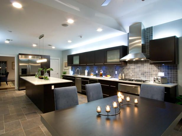 High-End Design The high-end appliances in this kitchen make it any cook's dream. The blue under-cabinet lighting allows the tile backsplash to shine, and the neutral tones in the kitchen create a striking contrast against the dark-toned cabinets. Design by Vanessa DeLeon