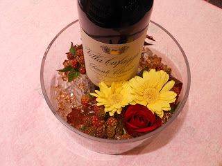 flaske i glas skål med blomster
