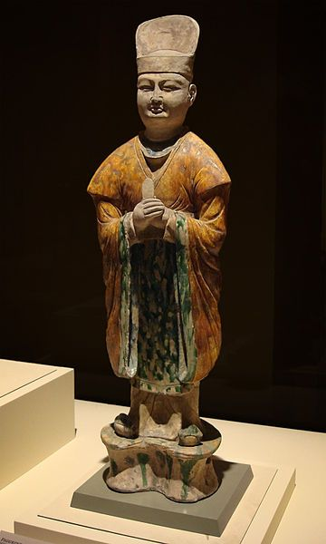 """Tri-coloured figure of a civil official Tang Dynasty (A.D. 618 - 907) Excavated at Xi'an, Shaanxi Province, 1957 This figure depicts the typical clothing of a Tang Dynasty official; tall hat, wide-sleeved outer garment tied at the waist with a wide belt, and rectangular """"kerchief"""" in front. A white inner gown hangs over his square shoes. He solemnly holds a tablet to his chest, preparing to provide a report to his superiors."""
