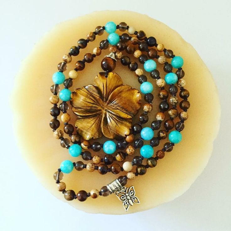 """108 bead hand-knotted Mala with 6mm Smokey Quartz, Tiger Eye and Picture Jasper beads and 8mm Brazilian Aquamarine. This Tiger Eye focal flower is so unique and beautiful! A mid-length Mala that hangs at about 18"""""""
