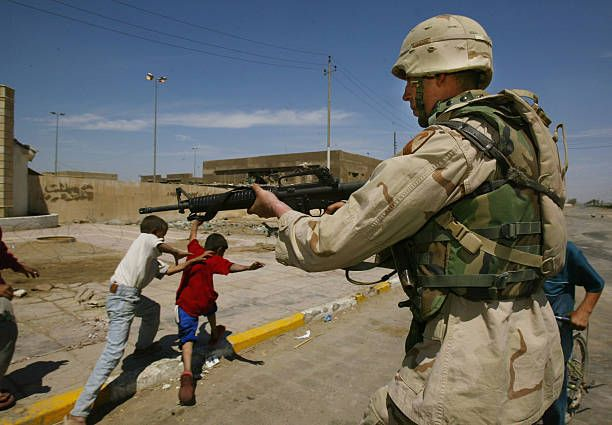 BAGHDAD, IRAQ - APRIL 8: U.S. Army Specialist David Newland from Palmdale, California with the 2-8 Regiment of the1st Armored Division Cavalry aims his gun to keep at Sadr City youths to make them keep their distance April 8,2004 in the Baghdad suburb of Sadr City in Iraq.