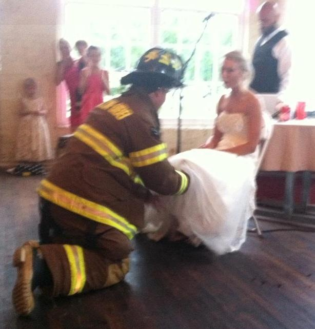 """Firefighter Garter Removal - Was so cute!  He came dancing in to the song """"I'm a fireman, that's my name"""", and did a """"smoke dive"""" for the garter!"""